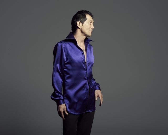 ブルーのサテンのシャツを着て立っている横顔の矢沢永吉の画像